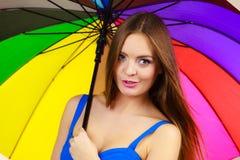 Γυναίκα που στέκεται κάτω από τη ζωηρόχρωμη ομπρέλα ουράνιων τόξων Στοκ Εικόνες
