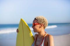 Γυναίκα που στέκεται με την ιστιοσανίδα στην παραλία στην ηλιοφάνεια στοκ φωτογραφία με δικαίωμα ελεύθερης χρήσης