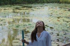 Γυναίκα που στέκεται μπροστά από τη λίμνη λουλουδιών λωτού στοκ εικόνες με δικαίωμα ελεύθερης χρήσης