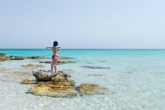 Γυναίκα που στέκεται σε έναν βράχο στη θάλασσα, με τις ανοικτές αγκάλες Στοκ Εικόνα