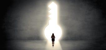 Γυναίκα που στέκεται σε μια μεγάλη κλειδαρότρυπα στοκ εικόνες