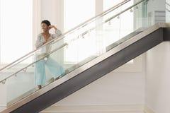 Γυναίκα που στέκεται στα σύγχρονα σκαλοπάτια γυαλιού Στοκ εικόνα με δικαίωμα ελεύθερης χρήσης