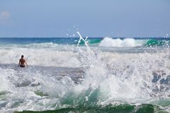 Γυναίκα που στέκεται στην κυματωγή της θάλασσας με τα μεγάλα κύματα Στοκ Εικόνες