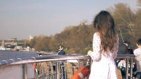 Γυναίκα που στέκεται στη γέφυρα ενός ποταμοπλοίου που περνά το πάρκο του Γκόρκυ στη Μόσχα απόθεμα βίντεο