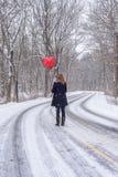 γυναίκα που στέκεται στη μέση του χιονισμένου δασώδους δρόμου που κρατά ένα ρ στοκ φωτογραφία
