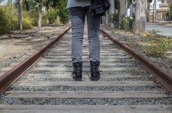 Γυναίκα που στέκεται στις εγκαταλειμμένες ράγες στοκ εικόνες