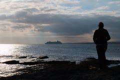 Γυναίκα που στέκεται στους βράχους και το κρουαζιερόπλοιο προσοχής στοκ εικόνα