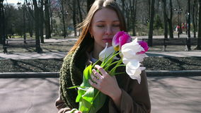 Γυναίκα που στέκεται στο πάρκο και που κρατά την ανθοδέσμη του λευκού απόθεμα βίντεο