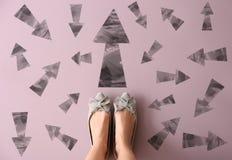 Γυναίκα που στέκεται στο υπόβαθρο χρώματος με τα βέλη που δείχνει στις διαφορετικές κατευθύνσεις Έννοια της επιλογής στοκ φωτογραφία