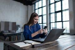 Γυναίκα που στέλνει τα μηνύματα κινητό app στο smartphone της Γυναίκα σπουδαστής που μαθαίνει σε απευθείας σύνδεση να προετοιμαστ Στοκ φωτογραφία με δικαίωμα ελεύθερης χρήσης