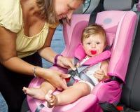 Γυναίκα που στερεώνει το γιο της σε ένα κάθισμα μωρών Στοκ εικόνες με δικαίωμα ελεύθερης χρήσης