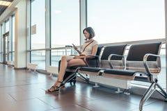 Γυναίκα που στηρίζεται στην αίθουσα άφιξης που περιμένει μια μεταφορά στον αερολιμένα στοκ εικόνα με δικαίωμα ελεύθερης χρήσης