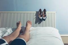 Γυναίκα που στηρίζεται στο κρεβάτι μετά από να περπατήσει στα υψηλά τακούνια στοκ φωτογραφία με δικαίωμα ελεύθερης χρήσης