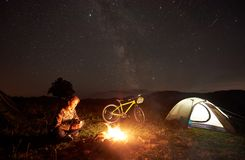 Γυναίκα που στηρίζεται τη νύχτα να στρατοπεδεύσει κοντά στην πυρά προσκόπων, σκηνή τουριστών, ποδήλατο κάτω από το σύνολο ουρανού στοκ εικόνες