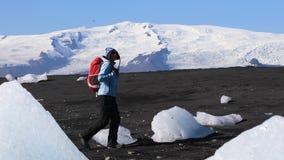 Γυναίκα που στη μαύρη παραλία παγόβουνων άμμου απόθεμα βίντεο