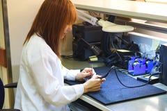Γυναίκα που συγκολλά έναν πίνακα κυκλωμάτων στο γραφείο τεχνολογίας της Κλείστε επάνω του θηλυκού μηχανικού στοκ εικόνα με δικαίωμα ελεύθερης χρήσης