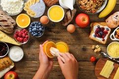 Γυναίκα που συμπιέζει τα πορτοκαλιά φρούτα και που κατασκευάζει το χυμό Κοριτσιών μαγειρεύοντας συστατικά προγευμάτων προγευμάτων στοκ εικόνα με δικαίωμα ελεύθερης χρήσης