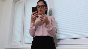 Γυναίκα που συμπιέζει τη σφαίρα πίεσης και που χρησιμοποιεί το smartphone απόθεμα βίντεο