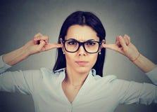 γυναίκα που συνδέει τα αυτιά της με τα δάχτυλα που ενοχλούνται από κάποιοη στοκ εικόνα