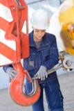 Γυναίκα που συνδέει το καλώδιο μετάλλων με το γερανό γάντζων στοκ φωτογραφία με δικαίωμα ελεύθερης χρήσης