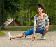 Γυναίκα που τεντώνει τα πόδια της στο πάρκο Στοκ εικόνα με δικαίωμα ελεύθερης χρήσης