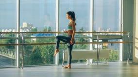 Γυναίκα που τεντώνει το πόδι της στην μπάρα Στοκ Εικόνες