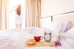 Γυναίκα που τεντώνεται στο δωμάτιο κρεβατιών μετά από το ξυπνητήρι και το ψωμί στο τ Στοκ φωτογραφίες με δικαίωμα ελεύθερης χρήσης