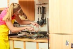 Γυναίκα που τηγανίζει την πασπαλισμένη με ψίχουλα cutlet μπριζόλα χοιρινού κρέατος στο τηγάνι τηγανητών Στοκ εικόνες με δικαίωμα ελεύθερης χρήσης