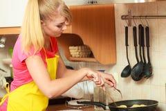 Γυναίκα που τηγανίζει την πασπαλισμένη με ψίχουλα cutlet μπριζόλα χοιρινού κρέατος στο τηγάνι τηγανητών Στοκ Φωτογραφίες