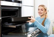 Γυναίκα που τοποθετεί τον ψήνοντας δίσκο στο φούρνο κουζινών στοκ εικόνες