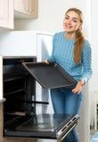 Γυναίκα που τοποθετεί τον ψήνοντας δίσκο στο φούρνο κουζινών στοκ φωτογραφία