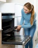 Γυναίκα που τοποθετεί τον ψήνοντας δίσκο στο φούρνο κουζινών στοκ εικόνα με δικαίωμα ελεύθερης χρήσης