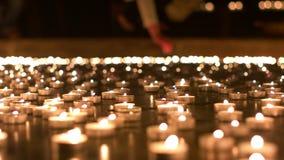 Γυναίκα που τοποθετεί το κερί της μεταξύ άλλων κεριών απόθεμα βίντεο