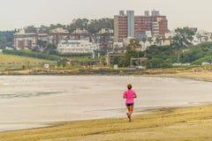 Γυναίκα που τρέχει στην ακτή της παραλίας Στοκ Εικόνα