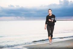 Γυναίκα που τρέχει στην παραλία στην ανατολή στοκ φωτογραφίες με δικαίωμα ελεύθερης χρήσης
