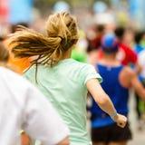 Γυναίκα που τρέχει το μαραθώνιο στην έναρξη ή τη γραμμή τερματισμού στοκ εικόνες