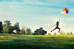 Γυναίκα που τρέχουν και μπαλόνια αφής άλματος που επιπλέουν στον ουρανό στον πράσινο τομέα χλόης και λουλουδιών στοκ εικόνες