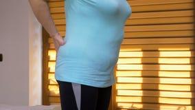 Γυναίκα που τρίβει τη χαμηλότερη πλάτη της που προσπαθεί να χαλαρώσει τον πόνο της φιλμ μικρού μήκους