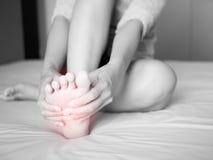 γυναίκα που τρίβει το επίπονο πόδι της, κόκκινο γεια-που ανάβει στην περιοχή πόνου Στοκ εικόνες με δικαίωμα ελεύθερης χρήσης