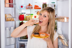 Γυναίκα που τρώει γλυκό doughnut κοντά στο ψυγείο Στοκ εικόνες με δικαίωμα ελεύθερης χρήσης