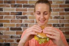 Γυναίκα που τρώει μεγάλο burger και το χαμόγελο Στοκ φωτογραφίες με δικαίωμα ελεύθερης χρήσης