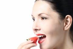 Γυναίκα που τρώει μια νόστιμη ώριμη κόκκινη φράουλα Στοκ Εικόνα