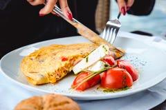 Γυναίκα που τρώει τα ανακατωμένα αυγά και το τυρί στο εστιατόριο Στοκ φωτογραφία με δικαίωμα ελεύθερης χρήσης