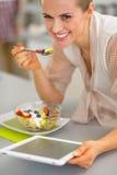 Γυναίκα που τρώει τη σαλάτα φρούτων και που χρησιμοποιεί το PC ταμπλετών Στοκ Εικόνα