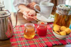 Γυναίκα που τρώει τη σπιτική μαρμελάδα φραουλών Δοχείο τσαγιού, μέλι, muffins στον πίνακα Στοκ φωτογραφία με δικαίωμα ελεύθερης χρήσης