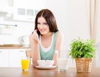 Γυναίκα που τρώει τη φράουλα με το γάλα και το χυμό από πορτοκάλι Στοκ Εικόνες