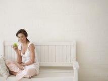 Γυναίκα που τρώει τη Apple στον πάγκο Στοκ Εικόνες