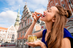 Γυναίκα που τρώει τις κλυπέες στην πόλη της Ρήγας Στοκ εικόνες με δικαίωμα ελεύθερης χρήσης
