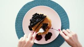 Γυναίκα που τρώει τις τηγανίτες μούρων με το μαχαίρι και το δίκρανο, τοπ άποψη, πρόγευμα πρωινού φιλμ μικρού μήκους