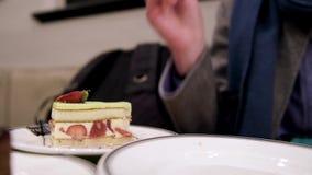 Γυναίκα που τρώει το εύγευστο κέικ φραουλών στον καφέ του Paul απόθεμα βίντεο
